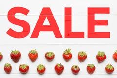 在白色木桌上绘的词销售 无缝的草莓 库存图片