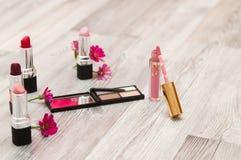 在白色木桌套装饰化妆用品,木背景的不同的构成化妆用品 睫毛卷发的人和铅笔lipst 库存图片
