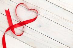 在白色木桌的情人节心形的丝带 免版税库存照片