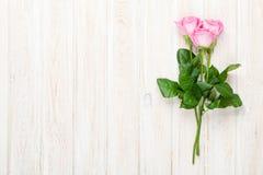在白色木桌的桃红色玫瑰花束 免版税库存图片