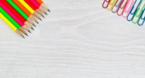 在白色木桌面上的明亮的五颜六色的铅笔和纸夹 库存照片