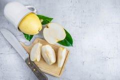 在白色木桌面的新鲜的nashi梨果子在a的一个一半 免版税库存图片