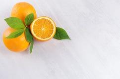 在白色木桌,顶视图,拷贝空间上的明亮的黄色成熟水多的桔子 库存照片