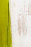 在白色木的绿色餐巾 库存照片
