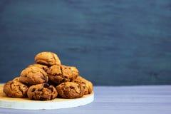 在白色木立场和蓝色,紫色背景的巧克力曲奇饼 免版税图库摄影
