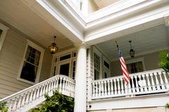 在白色木美国家庭门廊之外的美国国旗在查尔斯顿南卡罗来纳 免版税库存图片