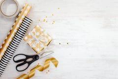在白色木老背景的金黄被加点的纸和包装用材料包裹的礼物盒 空的空间 免版税库存照片