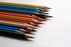 在白色木背景关闭的颜色铅笔 对角arrangementn 图库摄影