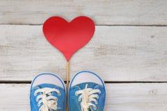 在白色木背景和红色心脏的浅蓝色运动鞋 图库摄影