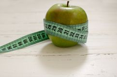 在白色木背景机智的厘米包裹的绿色苹果 免版税库存照片