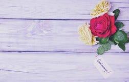在白色木背景的三朵开花的玫瑰 库存照片