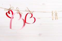 在白色木背景的三纸心脏,情人节贺卡的概念 图库摄影