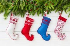 在白色木背景的五颜六色的圣诞节袜子与圣诞节杉树 抽象空白背景圣诞节黑暗的装饰设计模式红色的星形 免版税库存照片