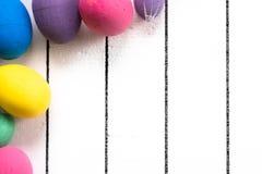 在白色木背景的五颜六色的生态聚苯乙烯泡沫塑料复活节彩蛋 与空间的框架写的文本 库存图片