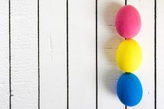在白色木背景的五颜六色的生态聚苯乙烯泡沫塑料复活节彩蛋 与空间的框架写的文本 免版税库存照片