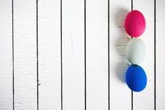 在白色木背景的五颜六色的生态聚苯乙烯泡沫塑料复活节彩蛋 与空间的框架写的文本 免版税库存图片
