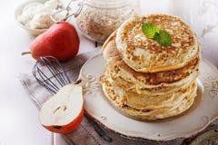 在白色木背景的健康燕麦薄煎饼 库存图片