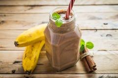 在白色木背景的健康香蕉和巧克力圆滑的人 库存照片