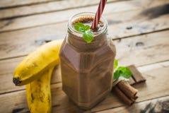 在白色木背景的健康香蕉和巧克力圆滑的人 库存图片