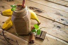 在白色木背景的健康香蕉和巧克力圆滑的人 免版税库存图片