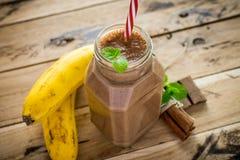 在白色木背景的健康香蕉和巧克力圆滑的人 免版税图库摄影