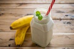 在白色木背景的健康香蕉圆滑的人 图库摄影