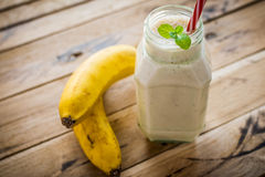 在白色木背景的健康香蕉圆滑的人 库存照片