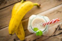 在白色木背景的健康香蕉圆滑的人 库存图片
