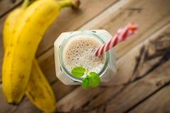 在白色木背景的健康香蕉圆滑的人 免版税库存照片