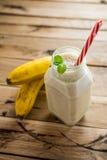 在白色木背景的健康香蕉圆滑的人 免版税图库摄影