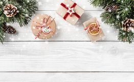 在白色木背景的圣诞礼物箱子与冷杉分支,杉木锥体 库存图片