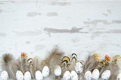 在白色木背景的复活节彩蛋装饰的和羽毛 书刊上的图片模板的复活节嘲笑 平的位置,顶视图 免版税库存照片