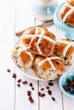 在白色木背景的复活节跨小圆面包 免版税库存图片