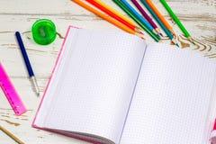 在白色木背景的学校用品围拢的室外笔记本与题字的空的空间 库存图片