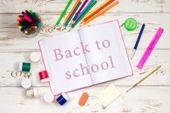 在白色木背景的学校用品围拢的室外笔记本与题字的空的空间 图库摄影