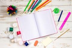 在白色木背景的学校用品围拢的室外笔记本与题字的空的空间 免版税库存图片