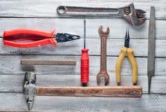 在白色木背景的工具:螺丝刀,钳子,小块,锤子,少年,文件,可调扳手 顶视图 免版税库存图片