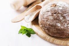 在白色木背景的新近地被烘烤的黑麦面包玉米棒 库存图片