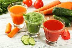 在白色木背景的新鲜的蕃茄、红萝卜和黄瓜汁 库存图片