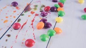 在白色木背景的熔化糖果 色的糖果 库存照片
