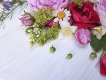 在白色木背景的玫瑰美好的花束雏菊生日框架 图库摄影