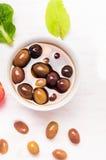 在白色木背景的用卤汁泡的橄榄 免版税库存图片