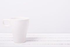 在白色木背景的白色茶杯 免版税图库摄影