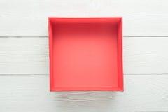 在白色木背景的空的红色箱子 免版税库存图片