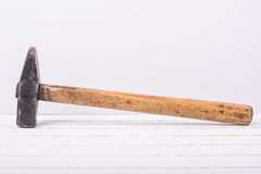 在白色木背景的老锤子 免版税库存照片