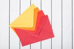 在白色木背景的色的信封 免版税库存图片