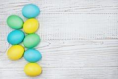 在白色木背景的色的鸡蛋 复活节的概念 免版税库存图片