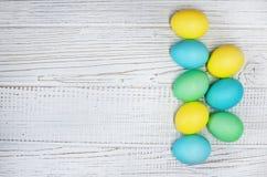 在白色木背景的色的鸡蛋 库存图片