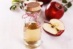 在白色木背景的苹果汁醋 免版税库存照片