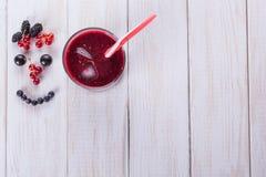 在白色木背景的莓果圆滑的人 从莓果的微笑 饮食食物概念 Copyspace 新鲜的莓果,蓝莓, 免版税库存图片